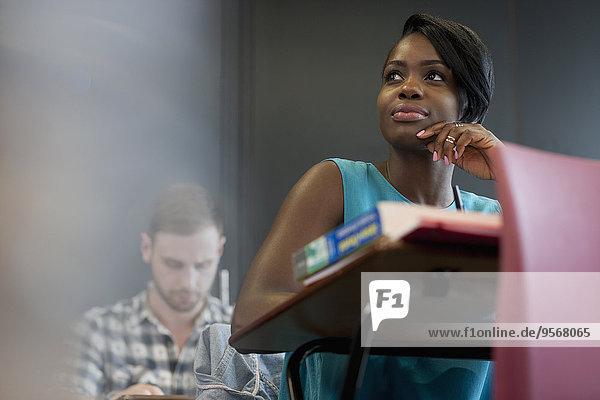 Student am Schreibtisch sitzend mit Hand am Kinn