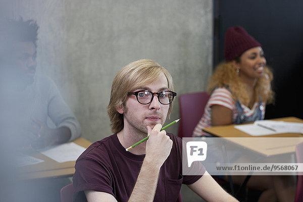 Porträt eines Studenten am Schreibtisch mit Hand am Kinn