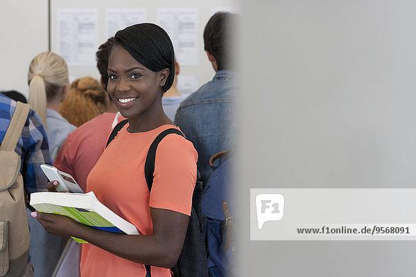 Porträt eines lächelnden Studenten im Flur  Menschen im Hintergrund beim Betrachten der Prüfungsergebnisse