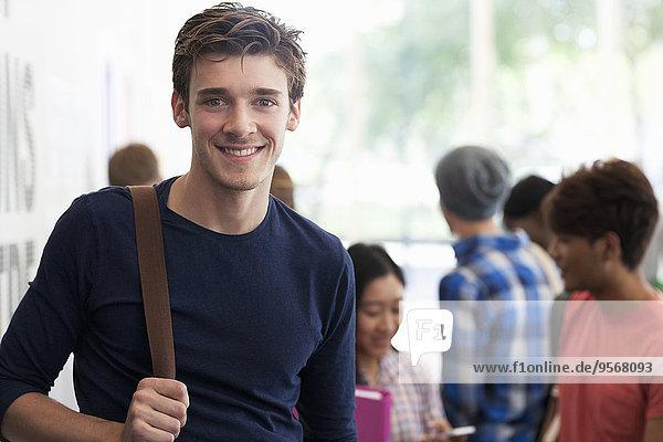 Porträt eines lächelnden Studenten  der in der Pause im Flur steht  Menschen im Hintergrund sprechend
