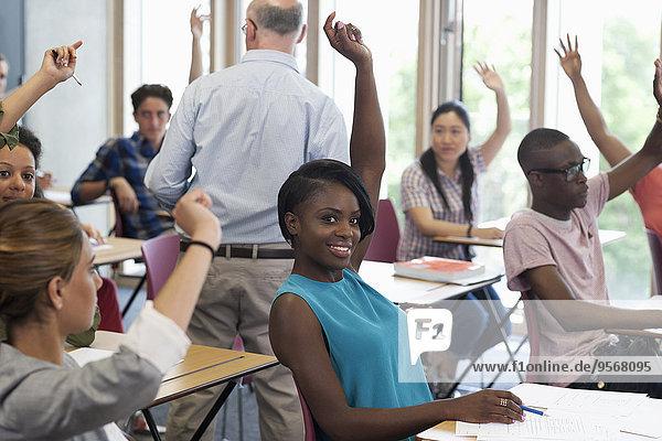 Universitätsstudenten heben Hände  um Professor zu antworten