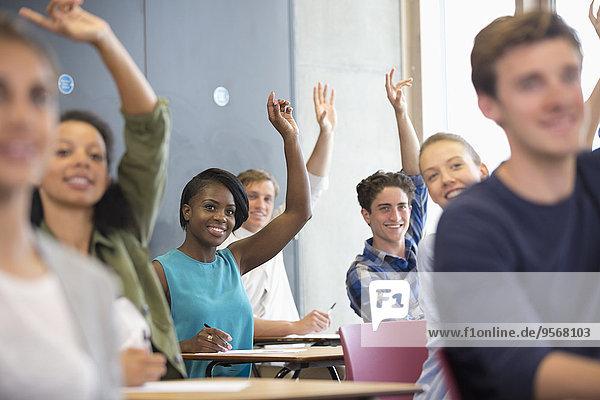 Universitätsstudenten heben die Hand beim Seminar