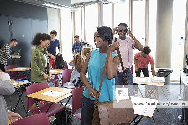 Universitätsstudenten packen ihre Koffer und verlassen das Klassenzimmer