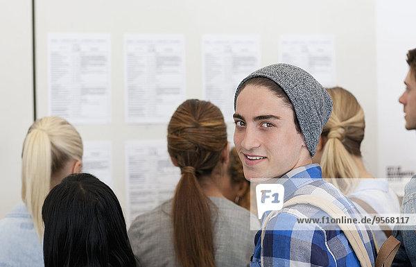 Männlicher Schüler lächelt in die Kamera  während andere das Schwarze Brett lesen.