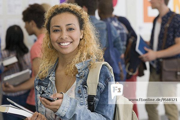 Lächelnde Studentin beim Telefonieren mit anderen Studenten im Hintergrund