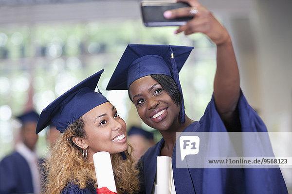 Zwei lächelnde Studentinnen  die sich nach dem Abschluss selbstständig machen.