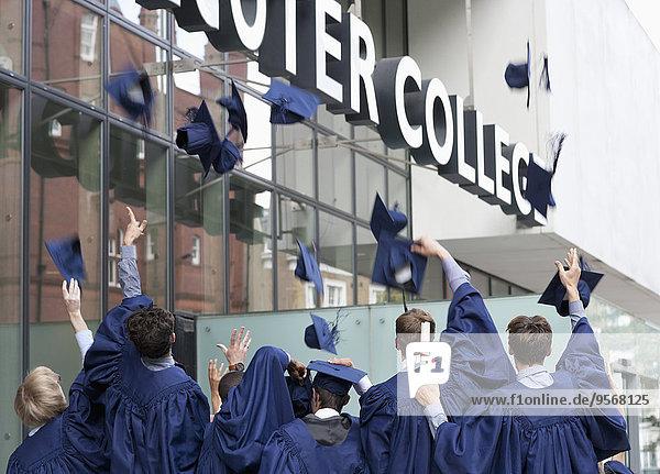 Gruppe von Schülern  die außerhalb des Colleges Abschlussfeierhüte werfen