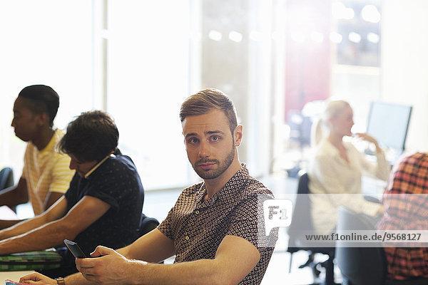 Männlicher Schüler sitzt am Schreibtisch im Klassenzimmer und benutzt das Handy.