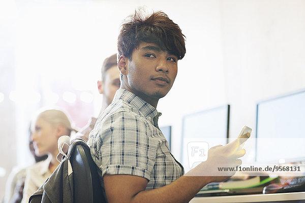 Männlicher Student sitzt am Schreibtisch mit dem Handy