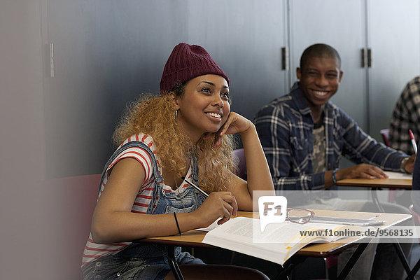 Studentinnen und Studenten  die während der Vorlesung lächelnd am Schreibtisch sitzen