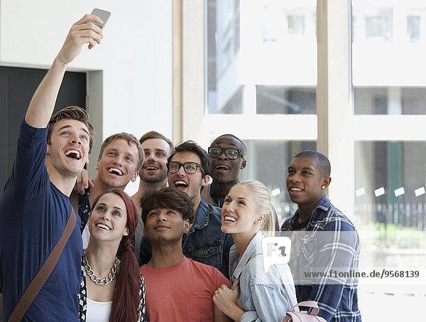 Gruppe von lachenden Schülern  die sich auf dem Flur mit großem Fenster im Hintergrund austoben