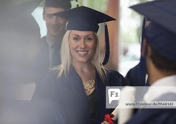 Eine Studentin lächelt in Abschlusskleidung  umgeben von anderen Studenten.
