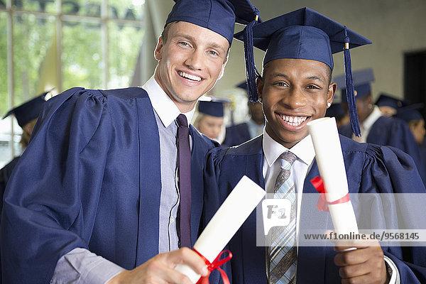 Zwei lachende männliche Studenten in Diplom-Kleidung