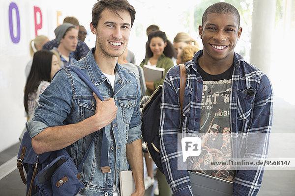 Zwei männliche Schüler lächeln vor der Kamera mit anderen Schülern im Hintergrund