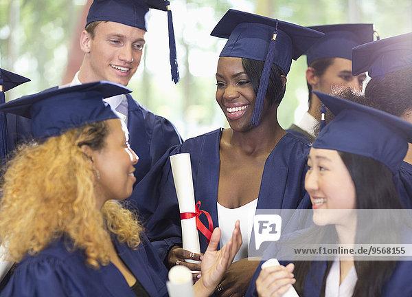 Gruppe von lächelnden Schülern in Abschlussfeier-Klamotten im Gespräch