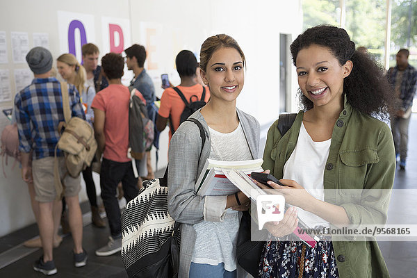 Porträt von zwei lächelnden Studentinnen mit Büchern  andere Studenten im Hintergrund