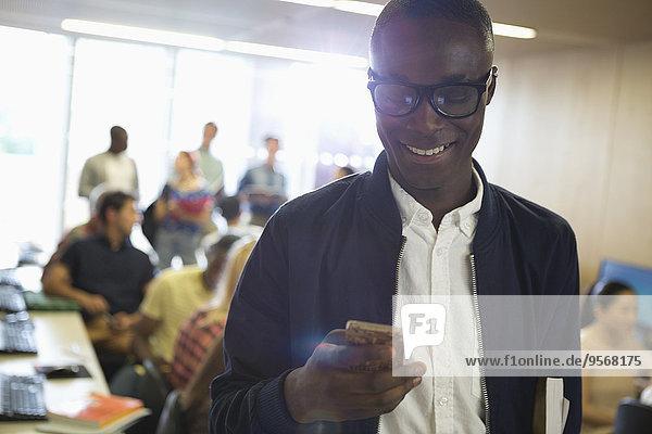 Lächelnder Schüler mit Brille  der auf das Smartphone schaut  mit anderen Schülern im Hintergrund
