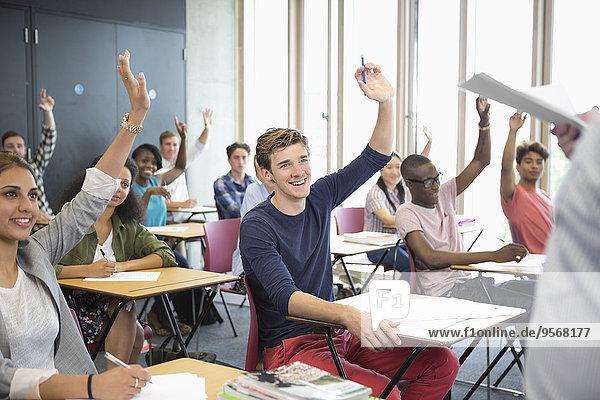 Blick auf lächelnde Schüler  die mit erhobenen Armen am Schreibtisch sitzen.