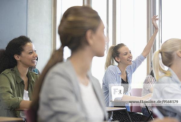 Blick auf lächelnde Schülerinnen am Schreibtisch im Klassenzimmer