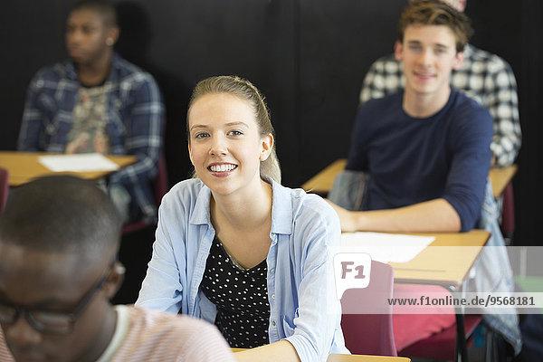 Blick auf lächelnde Schüler am Schreibtisch im Klassenzimmer