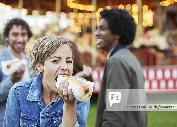 Drei junge Leute essen Hot Dogs im Vergnügungspark