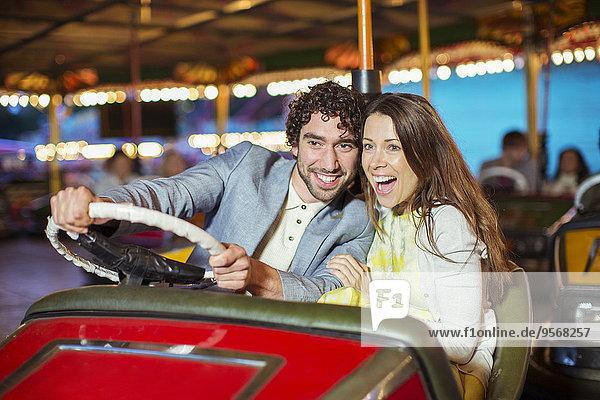 Paar auf Stoßstange Autofahrt im Vergnügungspark