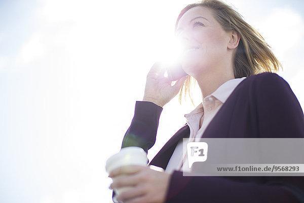 Low-Winkel-Ansicht der Geschäftsfrau im Gespräch auf dem Handy