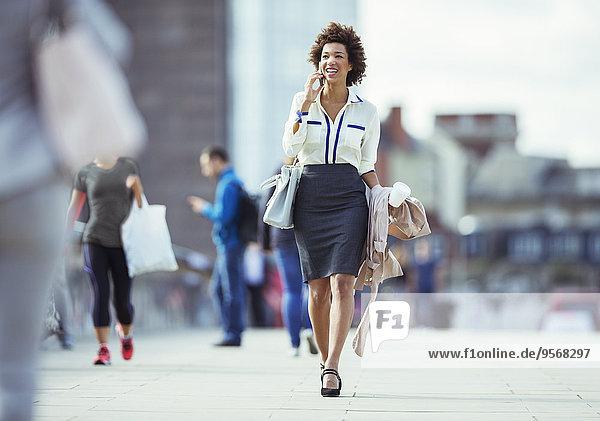 Geschäftsfrau im Gespräch am Handy in der Stadt