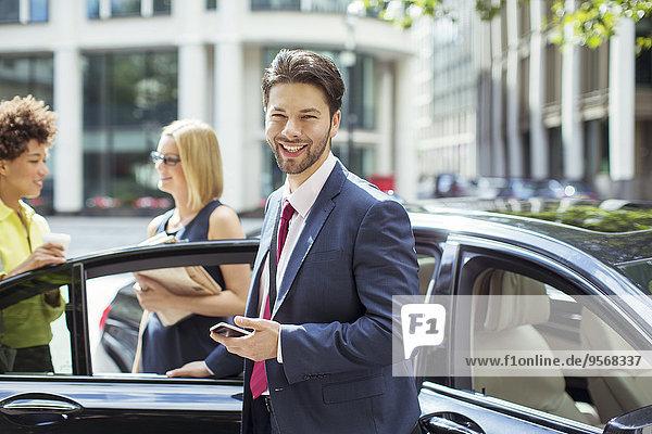 Geschäftsmann lächelt außerhalb des Autos