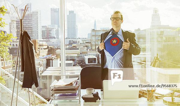 Geschäftsmann enthüllt Superheldenkostüm unter Anzug