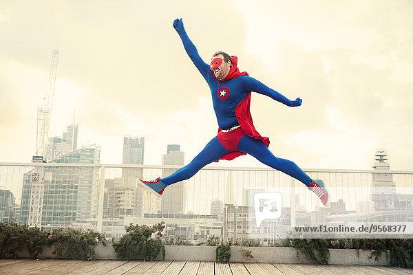 Superhelden springen auf dem Stadtdach