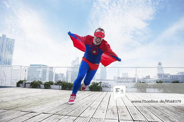 Superheldenlauf mit Umhang auf dem Stadtdach