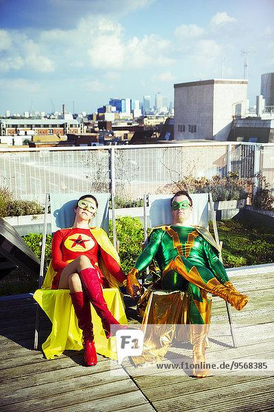 Superheldenpaar sitzt auf dem Dach der Stadt