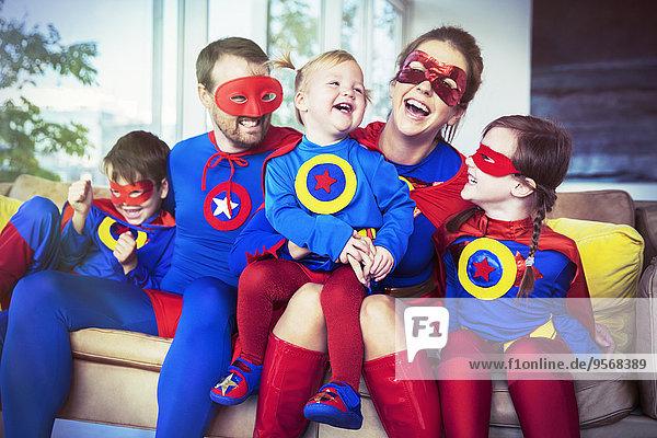 Superheldenfamilie lacht auf dem Sofa
