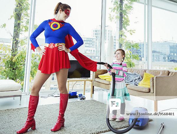 Tochter eines Superhelden  der ihren Umhang im Wohnzimmer absaugt.