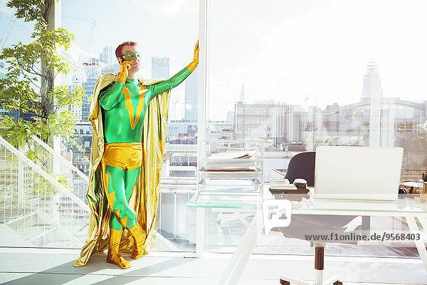 Superheld spricht im Büro auf dem Handy