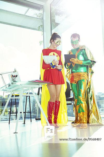 Superhelden bei der Arbeit mit dem digitalen Tablett im Büro