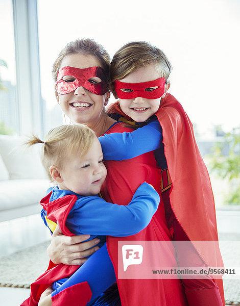 Superheldenmutter und Kinder umarmen sich im Wohnzimmer