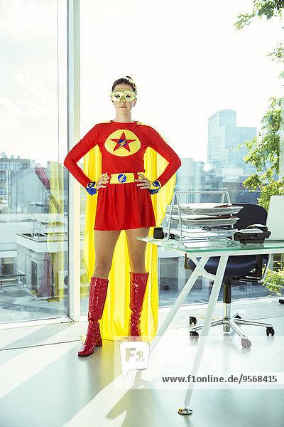 Superheld stehend mit Händen auf den Hüften im Büro