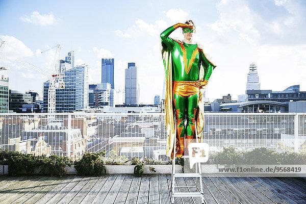Superheld mit Blick von der Stufenleiter auf das Stadtdach