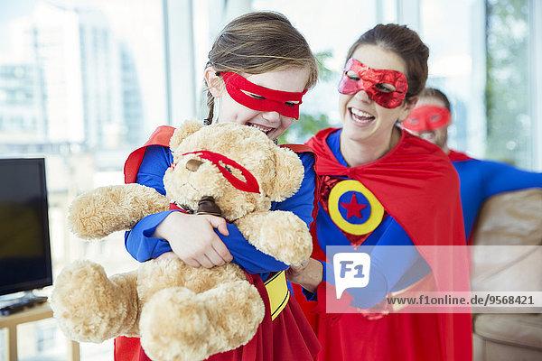Superheldenmutter und -tochter spielen mit Teddybären