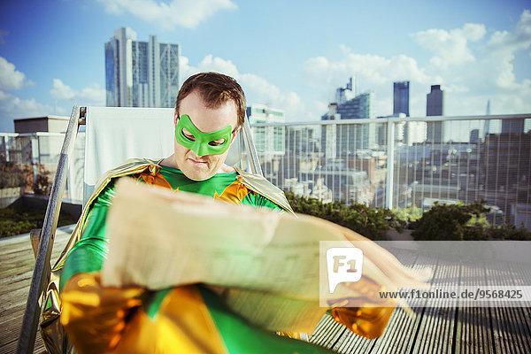 Superheld liest Zeitung auf dem Stadtdach