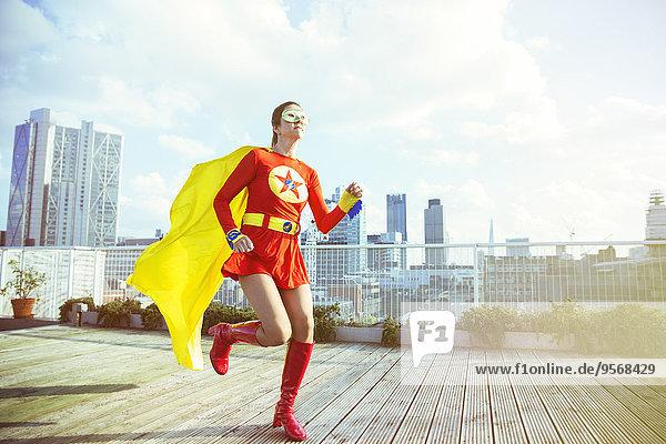 Superheld läuft auf dem Dach der Stadt