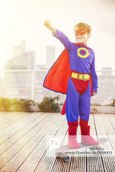 Superheldenjunge steht auf dem Skateboard auf dem Dach der Stadt