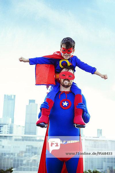 Superhelden-Vater mit Sohn auf den Schultern auf dem Dach der Stadt