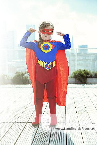 Superheldenmädchen beugt Muskeln auf dem Stadtdach