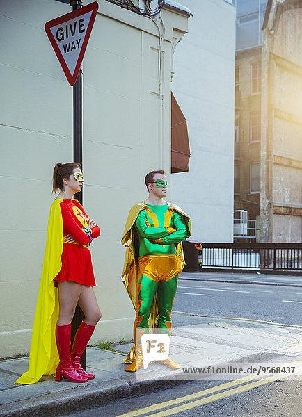 Superheldenpaar wartet an der Ecke auf dem Bürgersteig der Stadt