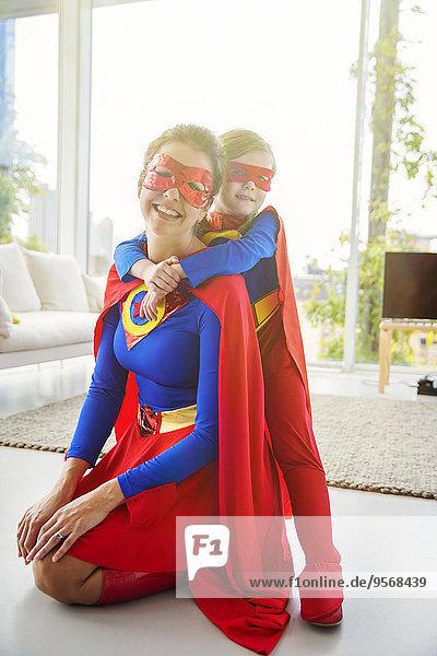 Superheldenmutter und Sohn lächeln im Wohnzimmer