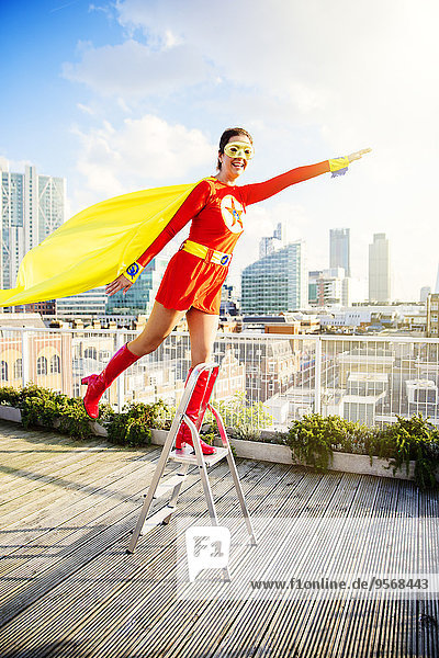 Superhero standing on stepladder on city rooftop
