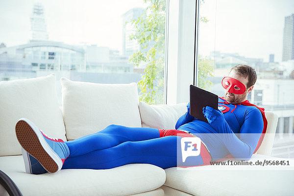 Superheld mit digitalem Tablett auf dem Wohnzimmersofa